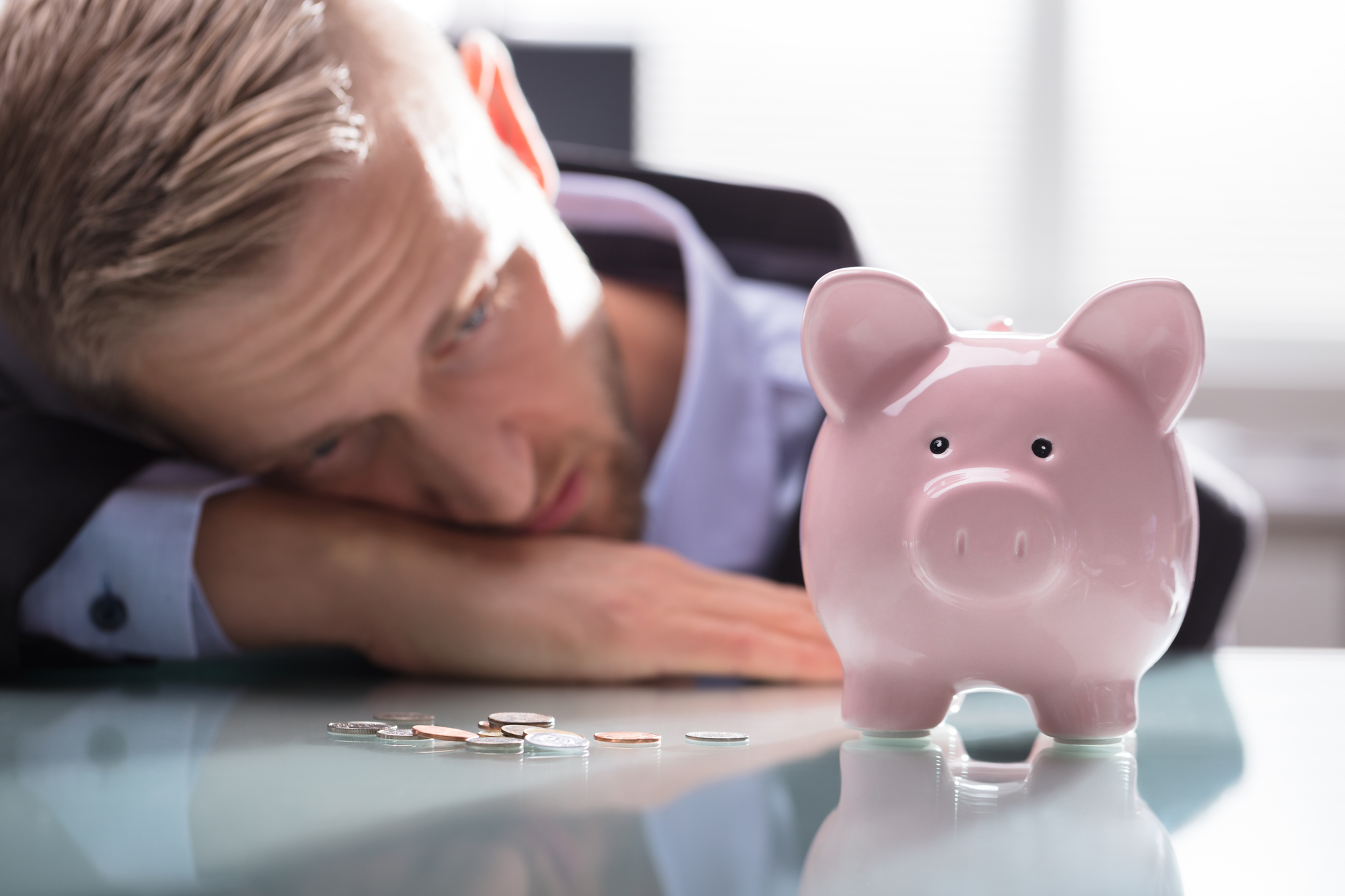 Close-up Of A Depressed Businessman Looking At Coins And Pink Piggybank On Reflective Desk
