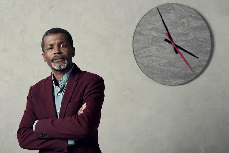 Confident african american businessman with crossed arms standing near wall with big clock