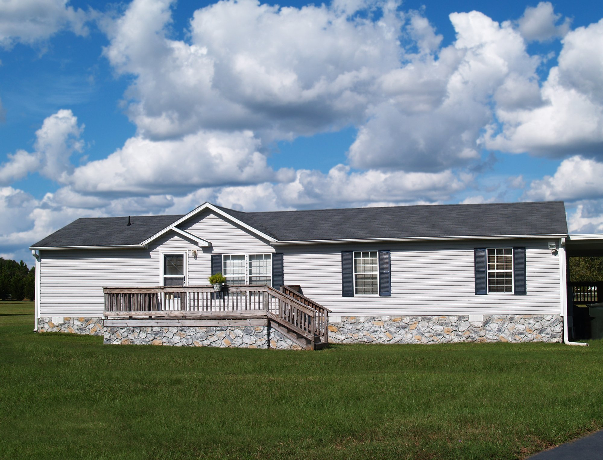 Gray trailer home with stone foundation or skirting and shutters in front of a beautiful sky
